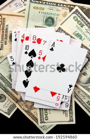Dollars and a deck of playing cards on black background close-up - stock photo