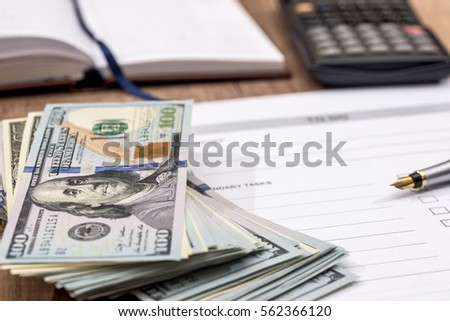 dollars and calculator with blank sheet on the table