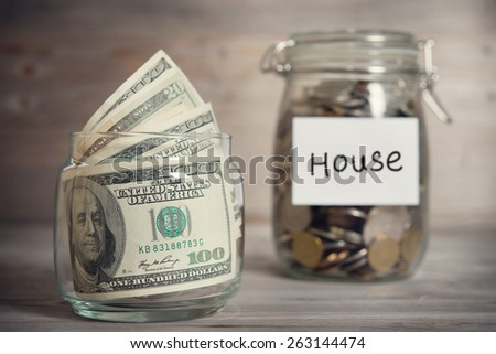 Dollars and coins in glass jar with house label, financial concept. Vintage tone wooden background with dramatic light.