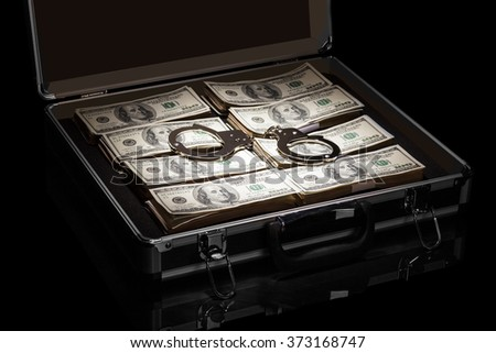 Dollars and handcuffs in suitcase isolated on black background