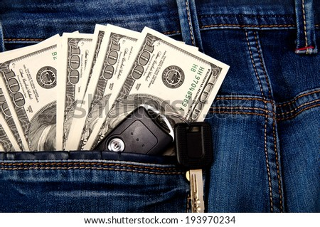 dollars and key from the car in the back pocket of jeans - stock photo