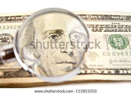 dollars and magnifying glass on a white background - stock photo