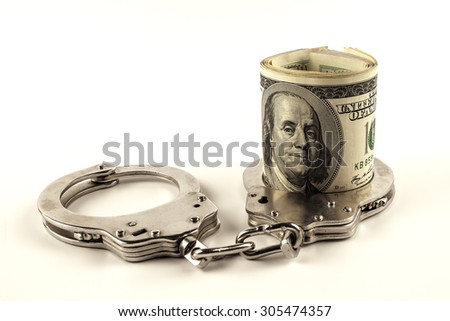 dollars and police handcuffs on a white background