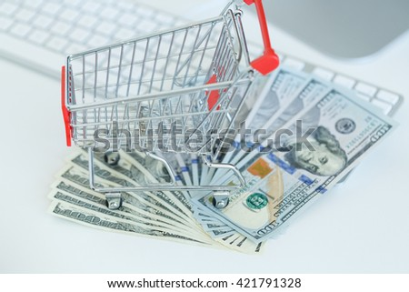 Dollars and shopping cart on a computer keyboard - concept of online shopping