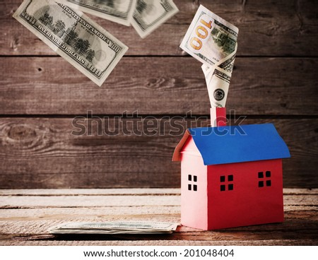 Dollars banknotes falling in house on wooden background - stock photo
