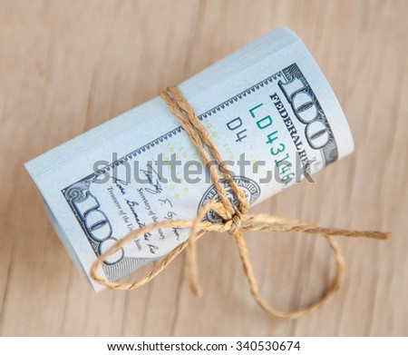 Dollars banknotes ties together, wooden background - stock photo