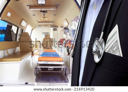 dollars bills in pocket of doctor presentation Inside of an ambulance for the hospital - stock photo