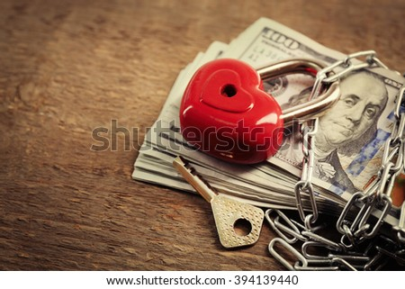 Dollars currency with lock and chain on wooden background - stock photo