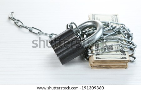 Dollars currency with lock and chain on wooden table - stock photo