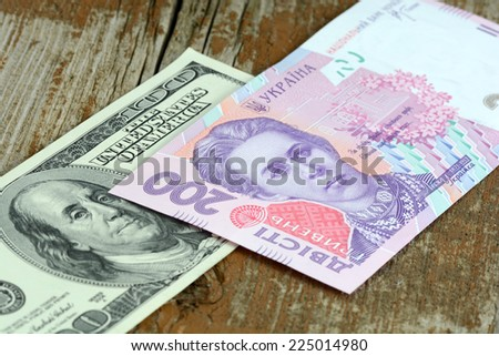 dollars euro hryvnia banknotes on wooden background - stock photo