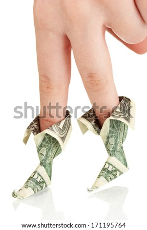 Dollars folded into boots on fingers of woman's hand isolated on white - stock photo