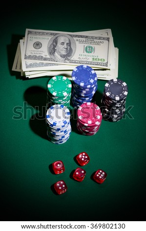 Dollars gambling chips and dices on green table