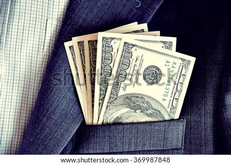 Dollars in the pocket of jacket (corruption, lobbying, bribery - concept). - stock photo