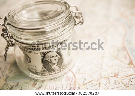 Dollars, magnifying glass, passport, sunglasses and a world map