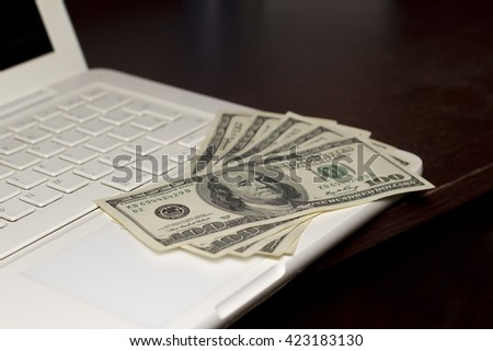 Dollars on a keyboard of notebook. Business concept