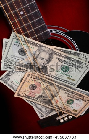 Dollars put between the strings of guitar. Earning money by music. Concept