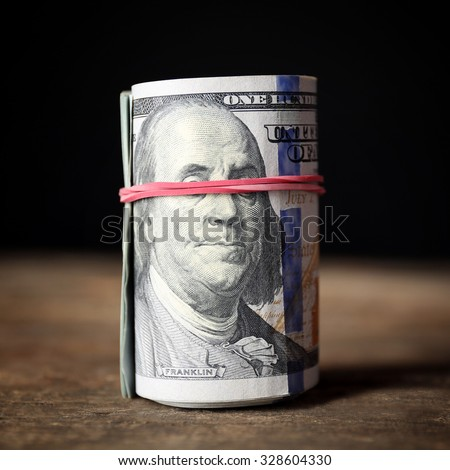 Dollars roll on wooden table in front of dark background - stock photo