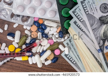 dollars with syringe and pills