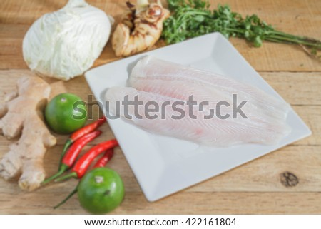 Dolly fish preparing for steaming fish with lime, chili, lettuce, ginger, galangal and parsley on wood table. - stock photo