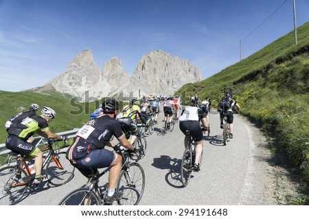 """DOLOMITE ALPS, ITALY-JULY 05, 2015:  Some of the participants of the """"Maratona dles Dolomites"""" bicycle road race in the mountains of the italian Dolomites at the first hours of the race. - stock photo"""