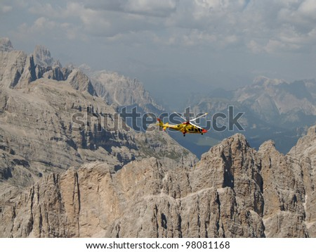 """DOLOMITES, ITALY - AUGUST 22: a helicopter of the Italian Alpin Rescue in mission on Mt Antelao to recover a climber tragically fell on the """"Canalone Oppel"""" on August 22, 2011 in Dolomites, Italy. - stock photo"""