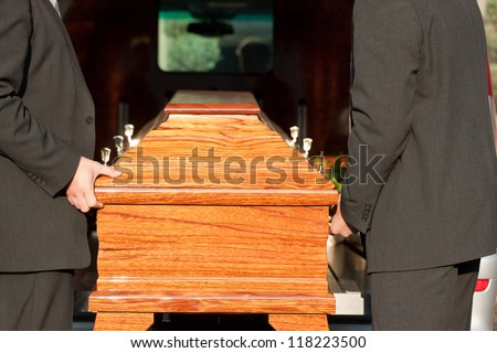 Dolor - Funeral with coffin on a cemetery, the casket carried by coffin bearer - stock photo