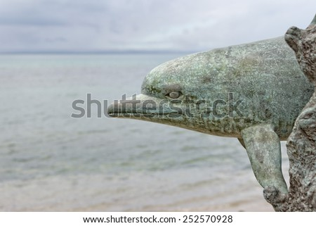 Dolphin copper statue by the sea