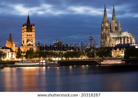 Dom and Great St. Martin church in Cologne at sunset lighting with reflection in river Rhine.