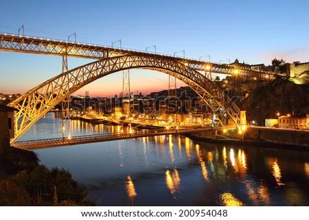 Dom Luis bridge at dusk and Porto cityscape in background. Portugal  - stock photo