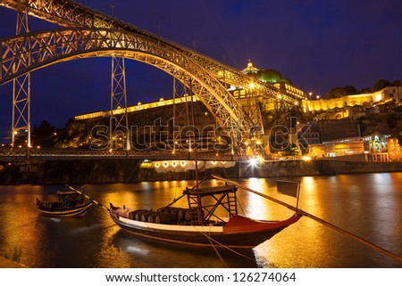 Dom Luis I bridge over Douro river and monastery of Serra do Pilar illuminated at night. Porto, Portugal. In first row some Rabelos, a type of boat traditionally used to transport wine barrels - stock photo