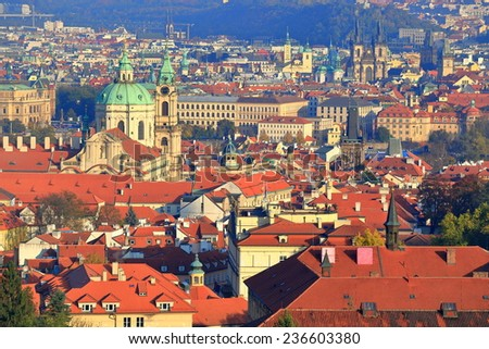 Dome of St Nicholas Church (Cathedral) surrounded by orange roof tops of Mala Strana, Prague, Czech Republic - stock photo