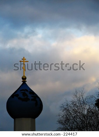 Dome of the Russian Orthodox Church in Berkeley, lit by late afternoon sun and silhouetted against darkly-clouded skies. - stock photo