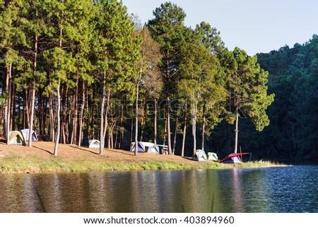 Dome tents near lake and pine trees in camping site at Pang Ung (Pang Tong reservoir), Mae Hong Son, Thailand - stock photo