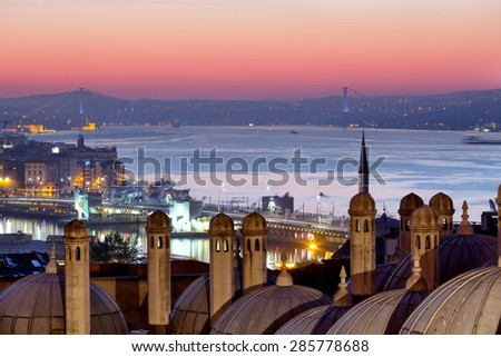 Domes of Suleymaniye Mosque and the bridge through Bosphorus at sunrise, Istanbul - stock photo