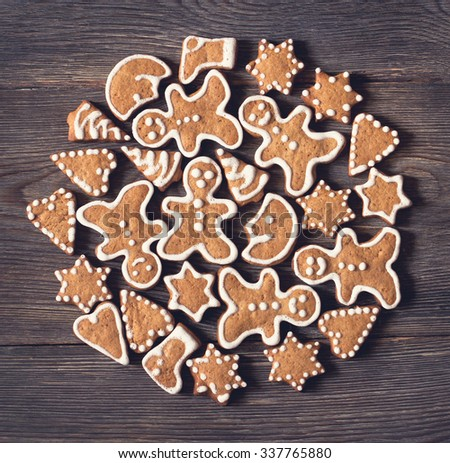 Domestic Christmas gingerbread cookies on old wooden background. Toned photo. - stock photo
