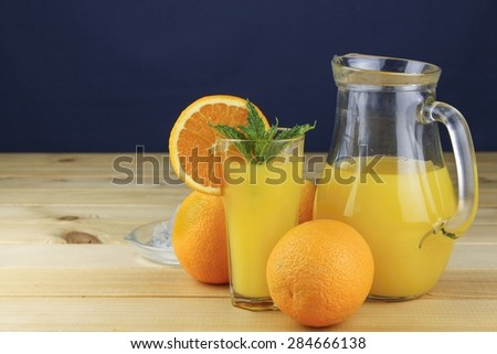 Domestic fresh orange juice in a glass jar on a wooden table. - stock photo