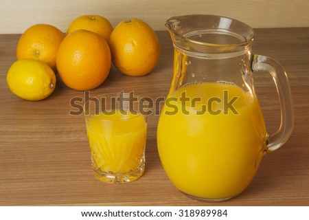 Domestic fresh orange juice in a glass jar on a wooden table. Hand-prepared homemade orange juice. Healthy drink for athletes. Place for your text. Sales of juices. - stock photo