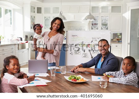 Domestic meeting in the kitchen, family looking to camera - stock photo
