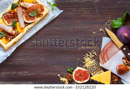 Domestic pie with prosciutto cheese and fig. Fresh food ingredients for cooking on old wooden board. - stock photo