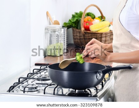 Domestic scene of anonymous woman cooking by the gas stove adding some broccoli  - stock photo