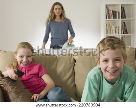 Domestic scene with mother ironing and children watching television - stock photo