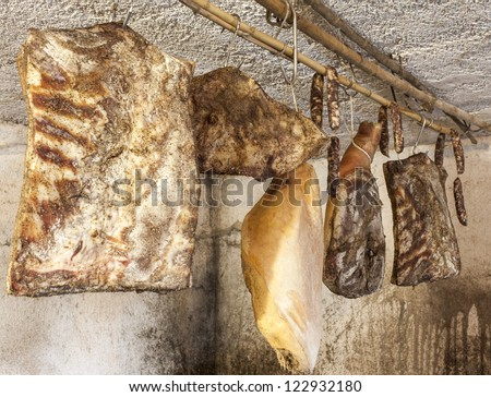 Domestic smoked meat products-delicatessen, drying in the traditional way in a old wine cellar - stock photo