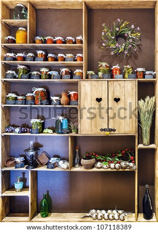 Domestic stocks with pickled vegetables in glass jars on wooden shelves