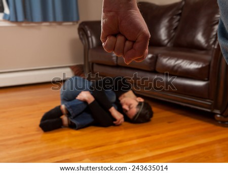 Domestic Violence Awareness - woman curled into fetal position in fear of partner - stock photo
