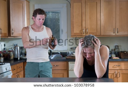 Domestic violence - beer-drinking man raging at and threatening woman - stock photo