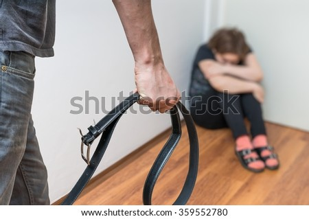 Domestic violence concept. Woman is abused by her husband with belt.