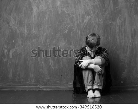 Domestic violence -  hopeless victim is sitting on the floor hugging her knees. Black and white - stock photo