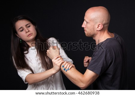 Domestic violence - husband  and wife are fighting, woman getting hold of man's fist