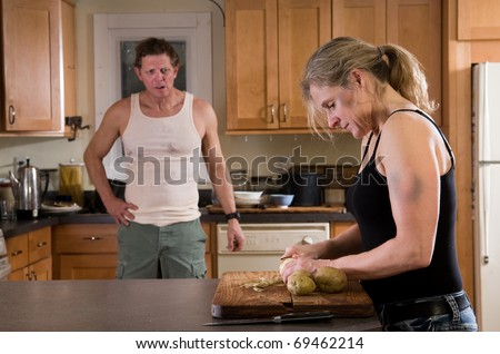 domestic violence - wide with bruises on arm and face peels potatoes while husband glowers at her - stock photo