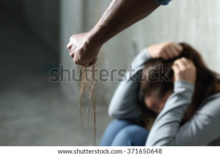 Domestic violence with a man hurting to a terrified woman pulling hair and holding it in the fist in a dark place - stock photo